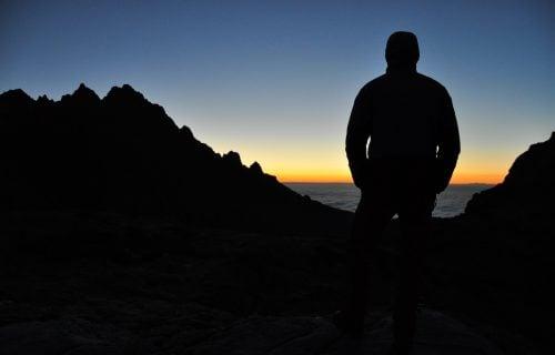 Man Overlooking Ocean On Mountains