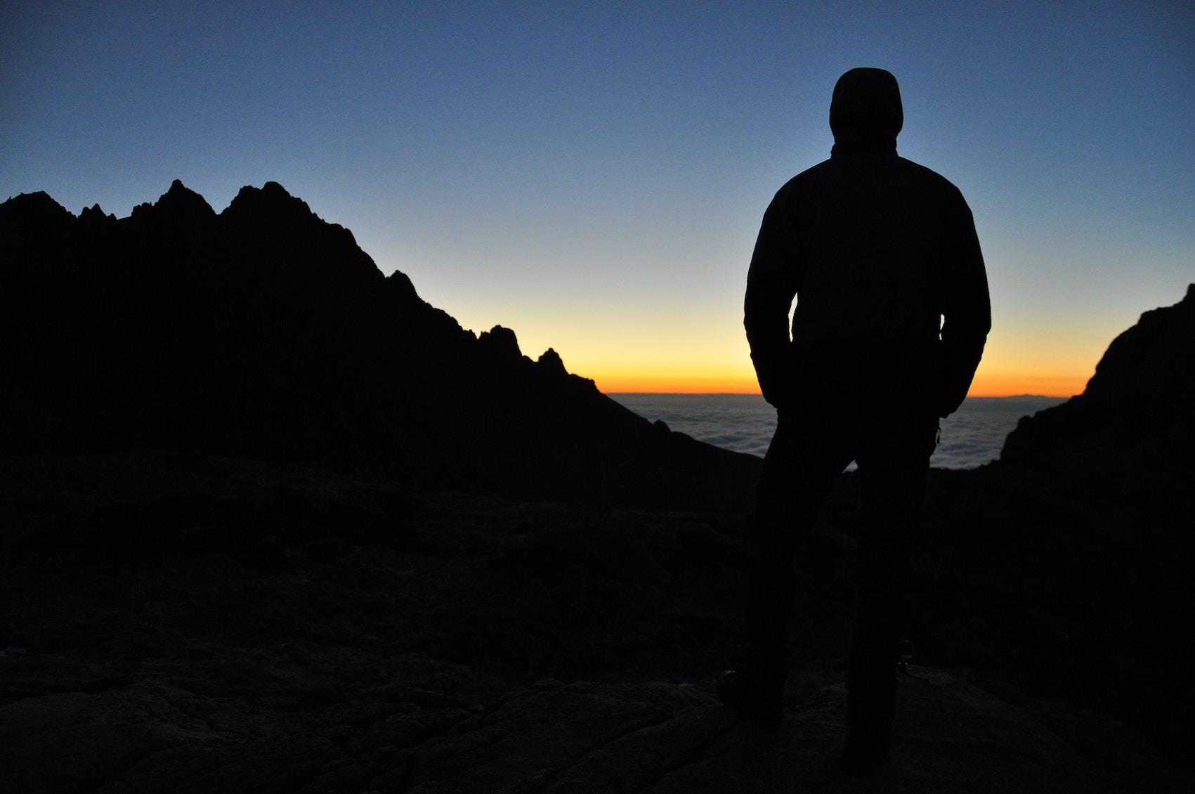 Man Overlooking Ocean Through Mountains