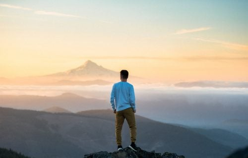 Man Looking Over Mountains At Peak Of Mountain